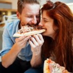 Couple Sharing Pizza And Eating At Home 1.jpg
